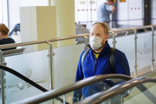 Young European Redbeard Man In  Blue Jacket, Protective Disposable Medical Mask In Airport.