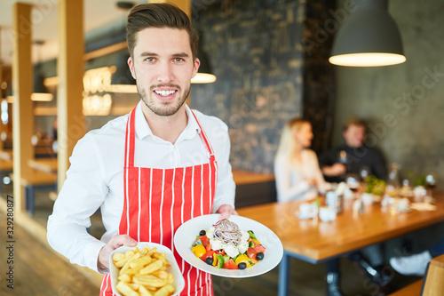 Leinwand Poster Kellner im Restaurant serviert Vorspeisen