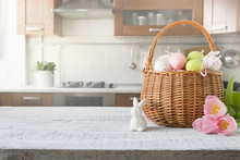 Wicker Basket With Bunny, Tulip, Easter Colorful Eggs On Kitchen Wooden Table. Spring Easter Composition. Space For Text.