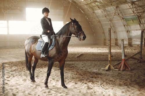 Woman on a horseback. Rider in a black uniform Wallpaper Mural