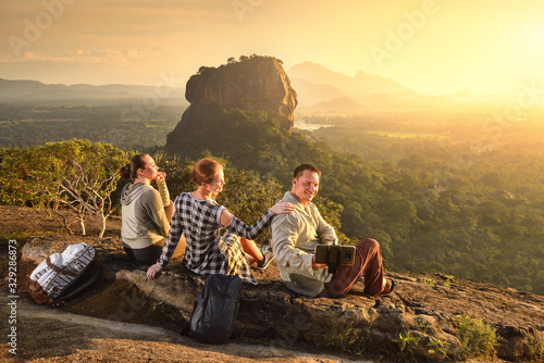 Group young tourists relaxes and watches during vacation colorful sunset on background of famous rocky plateau Lion peak, Sigiriya Fotobehang