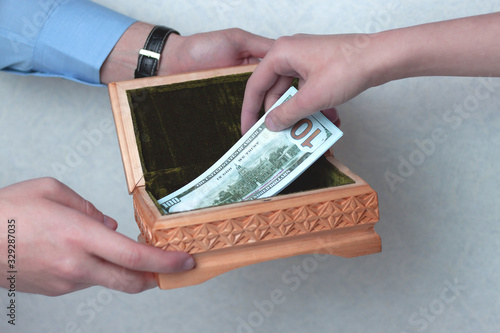 The hand puts the money in a box to store the accumulation Canvas Print