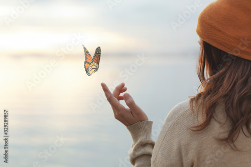Cuadros en Lienzo colorful butterfly is laying on a woman's hand