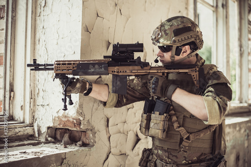 Cuadros en Lienzo Two men in military camouflage vegetato uniforms with automatic assault rifles