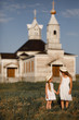 girls hold hands and stand against wooden Church