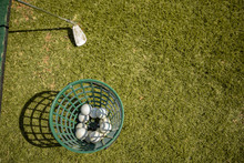 Golf Balls In A Basket And A Golf Club On The Grass.