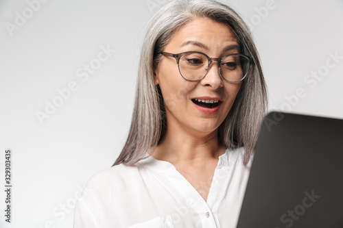 Fototapeta Image of adult mature woman wearing office clothes using laptop computer obraz