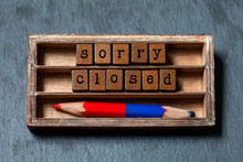 Sorry We Are Closed Concept. Vintage Box, Wooden Cubes Message With Old Style Letters, Red-blue Pencil. Gray Stone Background.