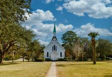 A Small White, Wooden Church Down Sidewalk Under Nice Sky
