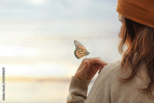 Foto colorful butterfly is laying on a woman's hand