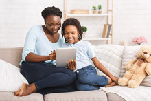 Happy Afro Family Spending Time Together Using Tablet