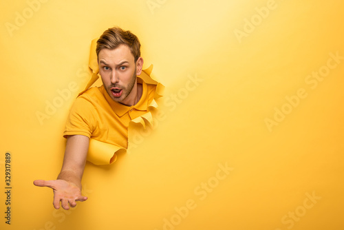 Obraz confused handsome man in yellow outfit in yellow paper hole - fototapety do salonu