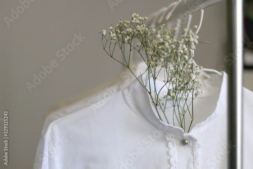 Collection of white shirts and blouses and gypsophila flowers on a clothing rack Canvas Print