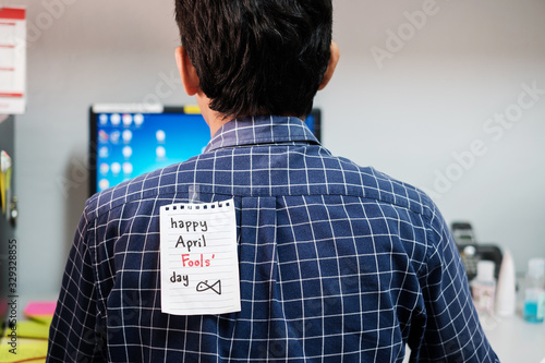 Photo Back of young man office with a white paper note attached with the text happy ap