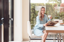 Enthusiastic Beautiful Young Woman Housewife Reads Her Favorite Newspaper In Kitchen While Drinking Tea. Young Woman Is Up To Date With World News. Modern Interior,large Windows Overlooking The Garden