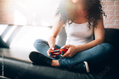young girl plays video games on a red joystick sitting on the couch