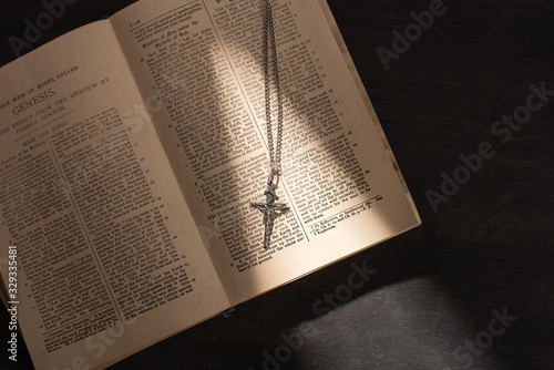 Obraz na plátně top view of open holy bible with cross on dark background with sunlight