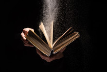 Cropped View Of Woman Holding Holy Bible With Dust On Black Background