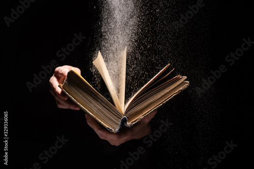 cropped view of woman holding holy bible with dust on black background Canvas Print