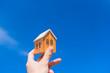 家を買うコンセプト。家のおもちゃを青空にかかげる。