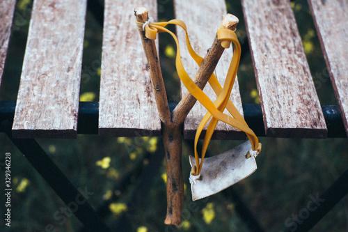 Vászonkép handmade slingshot and old wooden table. Rural scene.