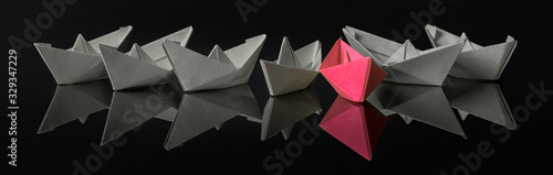 Foto Origami paper ship with sailboats, leadership, marketing concept, social media influencers, HR recruiter, disruptive innovation, standing out of the crowd concept