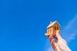 家の模型を青空にかかげる。住宅購入イメージ。憧れのマイホームを買う。