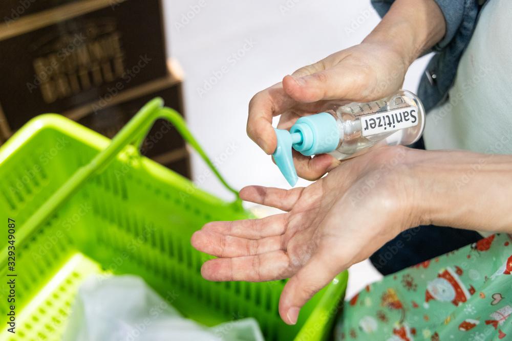 Fototapeta Asian shopper disinfecting hands with sanitizer in supermarket during shopping. Public shopping basket among high risk item.