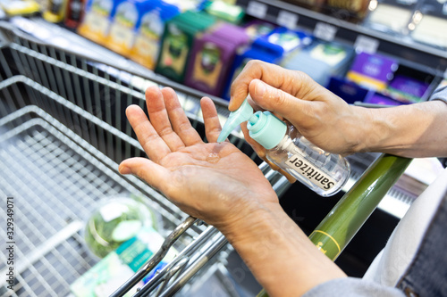 Asian shopper disinfecting hands with sanitizer in supermarket during shopping