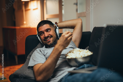 young man laying sofa and eating popcorn at his home