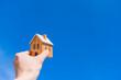 青空におもちゃの家を掲げる。住宅購入のコンセプト。