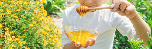 Fototapeta Child a plate of honey in the hands. Selective focus. obraz