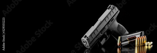 Black modern gun and ammunition for it on adark  background Fototapeta