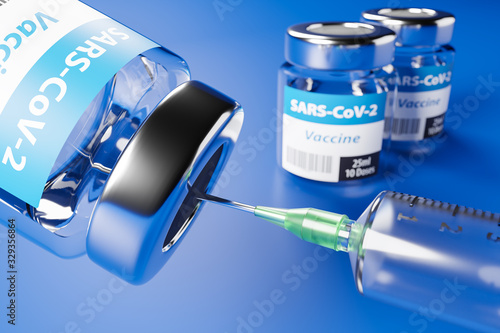 Vaccination against the new Corona Virus SARS-CoV-2: Two glass containers with 10 doses each and a syringe in front Canvas Print