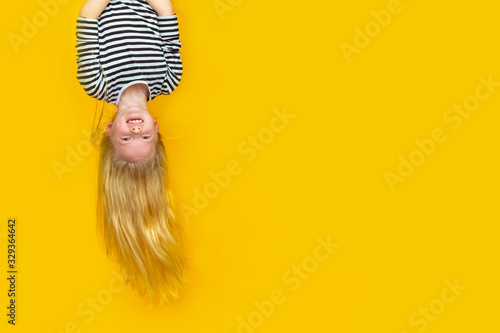Fototapety, obrazy: Excited crazy little blonde girl hanging happy upside down over isolated yellow studio background. Emotion, expression. Copy space for text.
