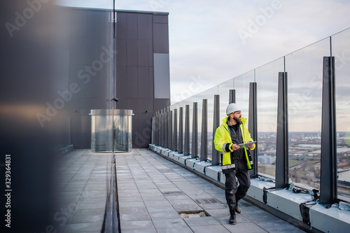 Man engineer walking on construction site, holding tablet. - 329364831
