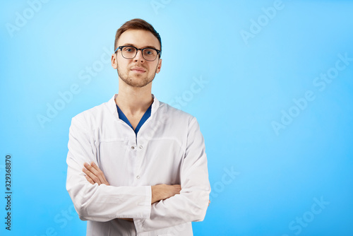 Portrait of intern doctor in white medical coat and glasses with a serious face expression isolated on blue wall background