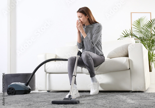 Young woman suffering from dust allergy while vacuuming house Wallpaper Mural
