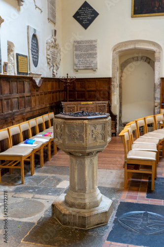 a stone baptismal font or baptism font in an old english church Wallpaper Mural