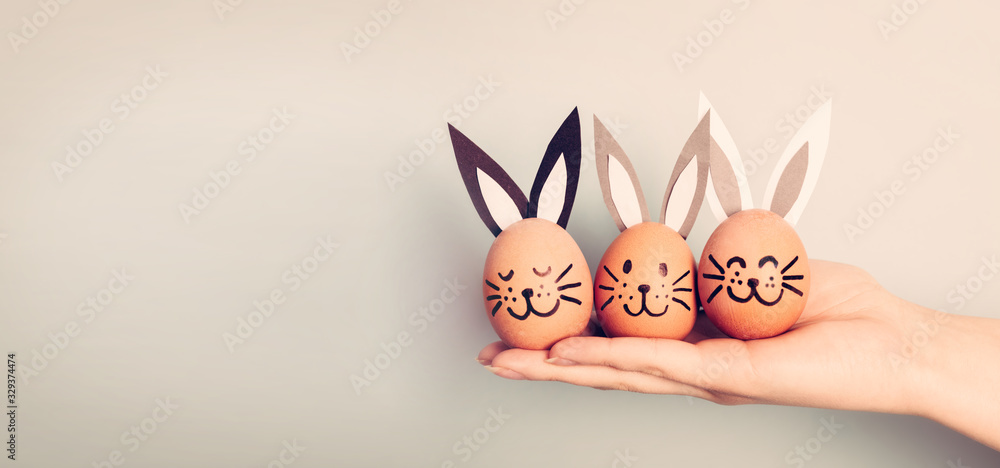 Fototapeta Three painted smiling Easter eggs bunnies on woman's hand