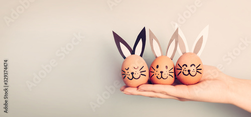 Photo Three painted smiling Easter eggs bunnies on woman's hand