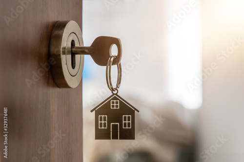 Fotografiet Open door to a new home with key and home shaped keychain