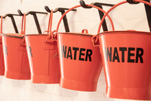 Red Buckets With The Word Water On The Side For Firefighting