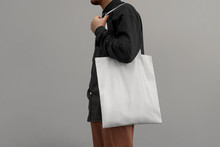 Urban Mockup Of Tote Bag. Men Holding Black Cotton Tote Bag On A Wall Background. Template Can Be Used For You Design