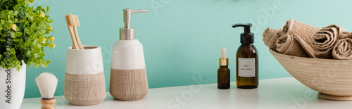 Fotografía Panoramic view of flowerpot, cosmetic and hygiene products near bowl with towels