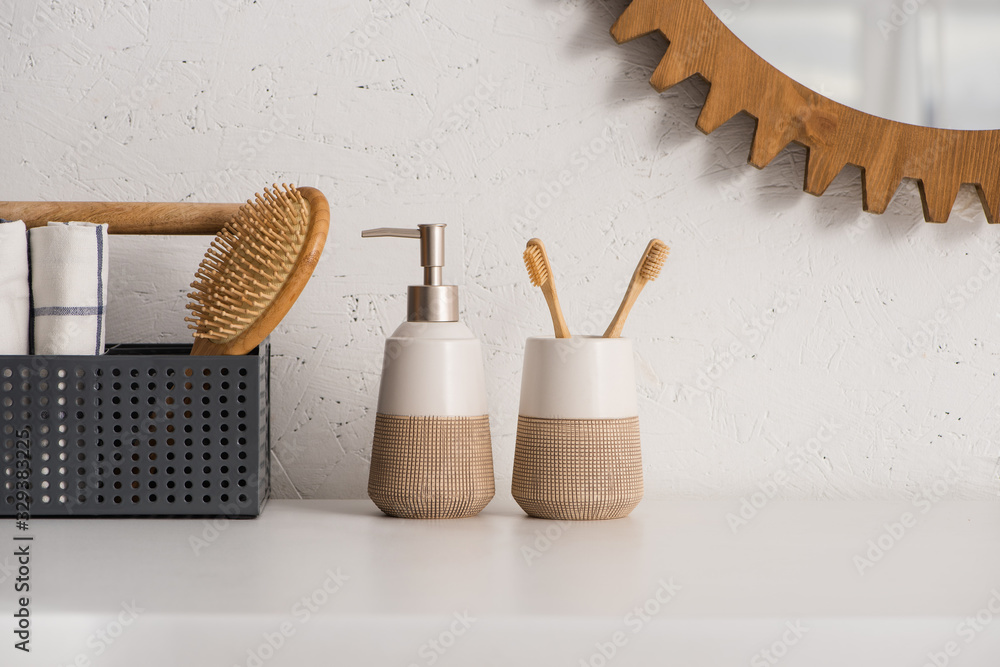 Fototapeta Box with hairbrush and towels near liquid soap and toothbrush holder with toothbrushes in bathroom, zero waste concept