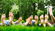 Family Relaxing On Green Grass, Barefoot Laying Down And Looking Into The Sky