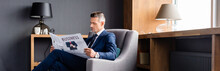 Panoramic Shot Of Businessman In Suit Reading Newspaper With Business Lettering