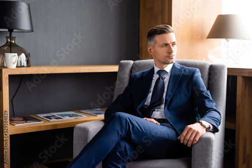 Fototapeta handsome businessman in suit sitting in armchair and looking away obraz