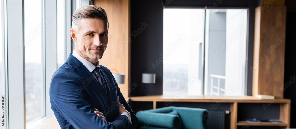 Fototapeta panoramic shot of smiling businessman in suit with crossed arms looking at camera in hotel